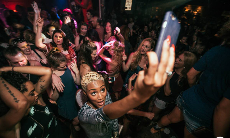 A woman taking a selfie and photo of the crowd, while she dances at The Basement, in Atlanta.