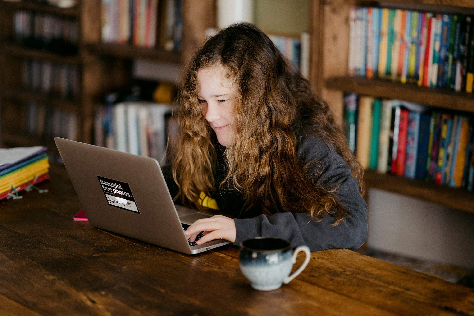 A girl sits at her laptop smiling, in a room of books.
