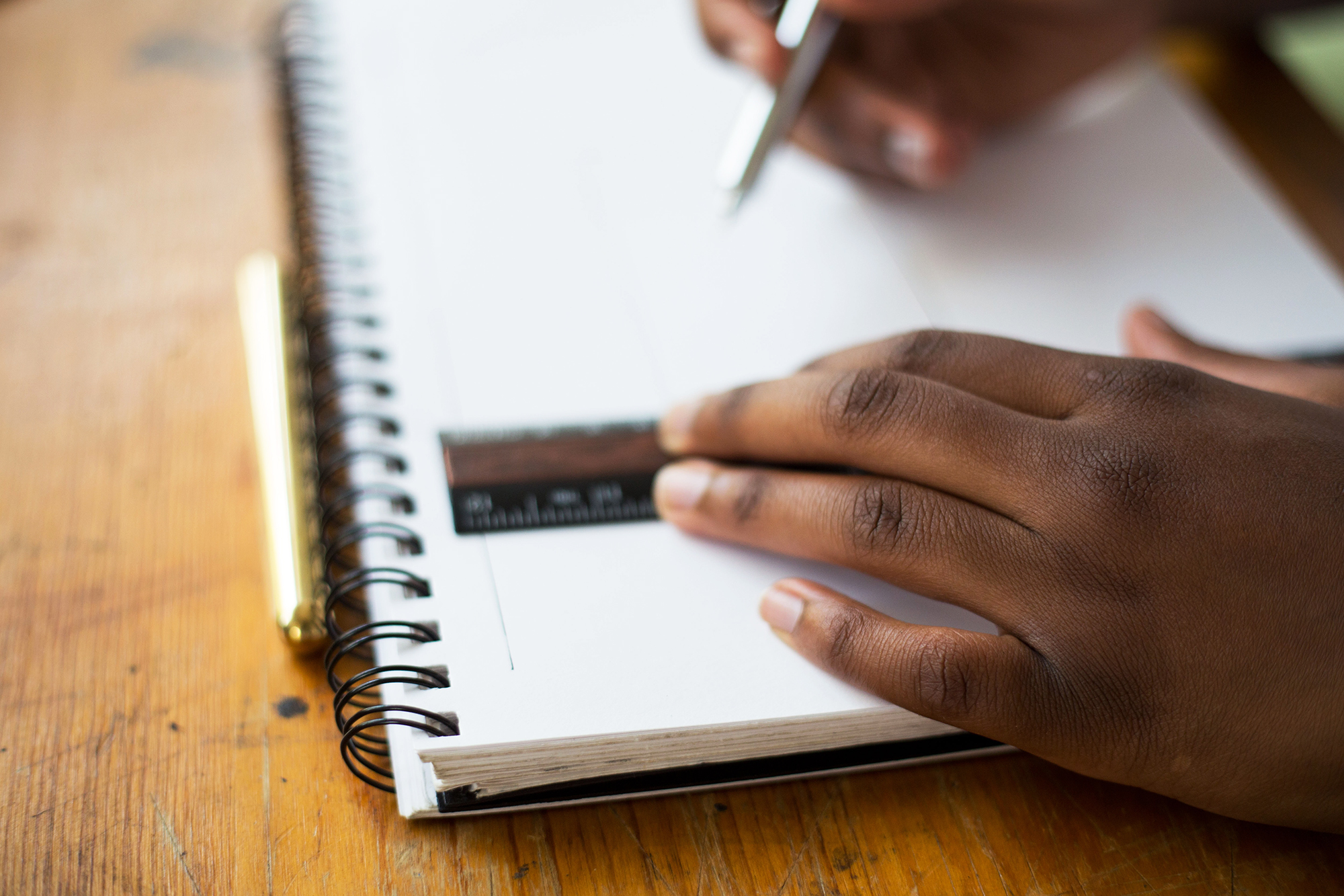 A teen's hands are shown drawing lines in a sketchbook with a pencil and ruler.