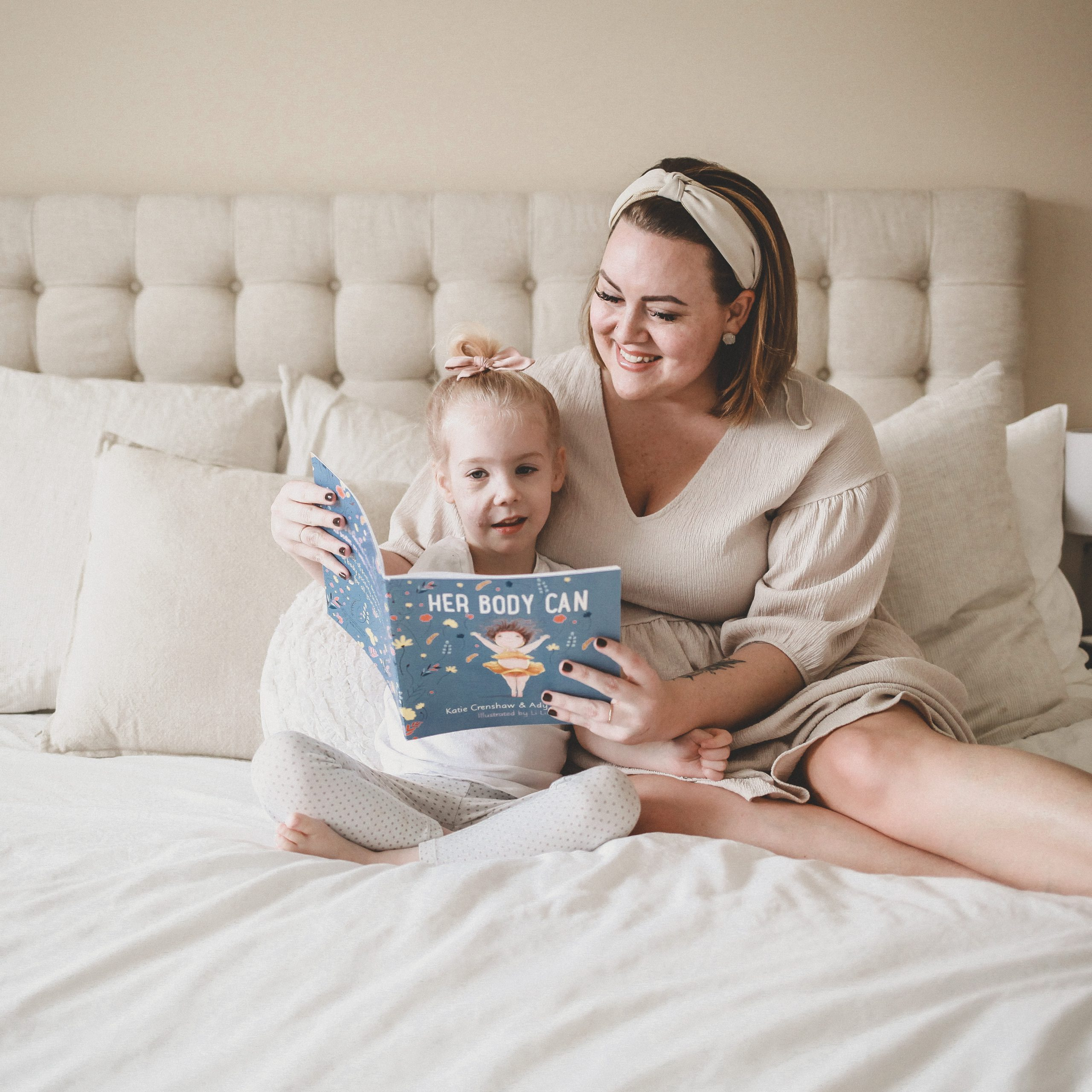 "Mom and author, Katie Crenshaw, sits on a bed with her daughter while they read her book, ""Her Body Can""."