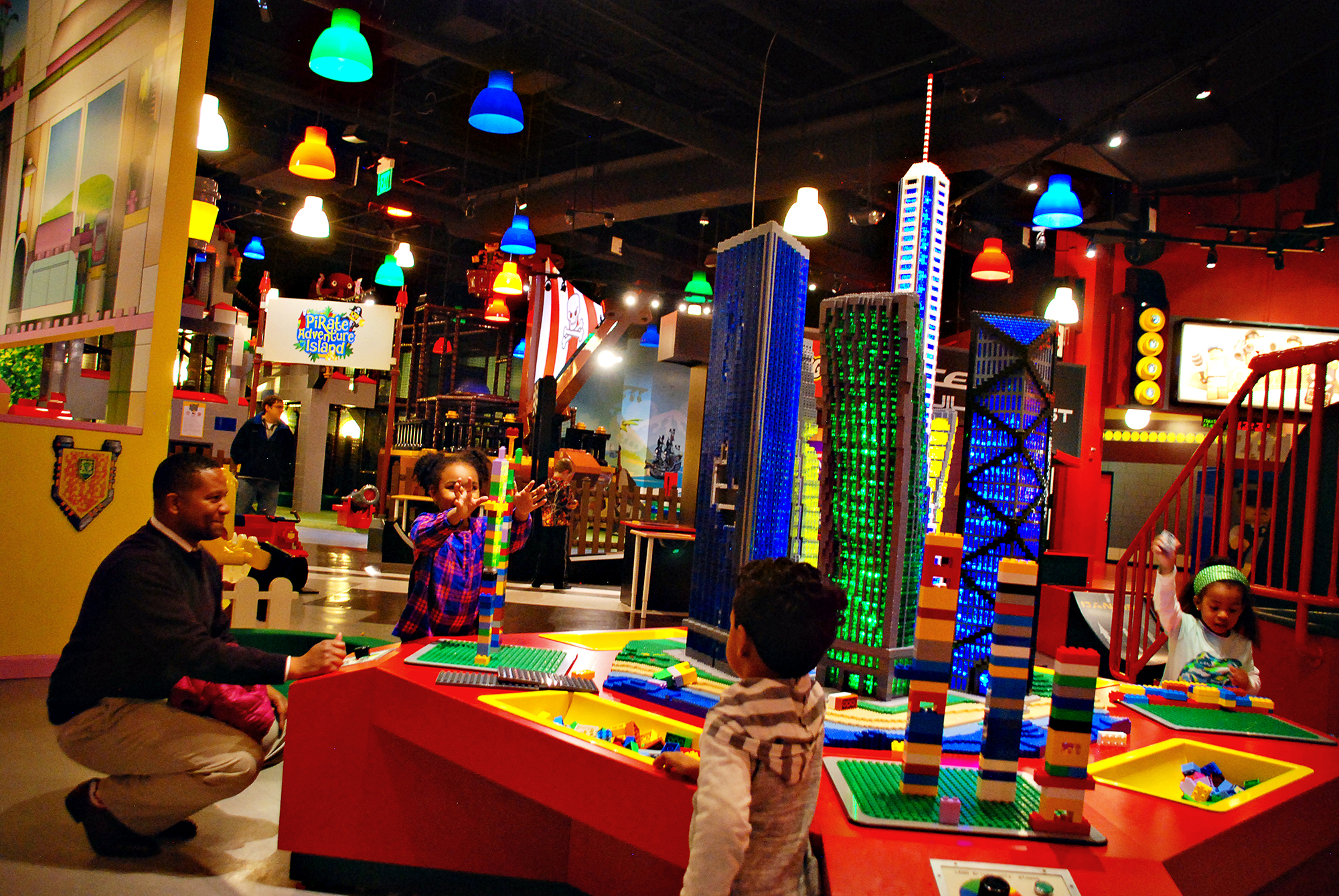 Kids and a guardian stand around a play space at LEGOLAND Discovery Center Atlanta, located at Phipps Plaza. They're building towers on bases that move and vibrate.