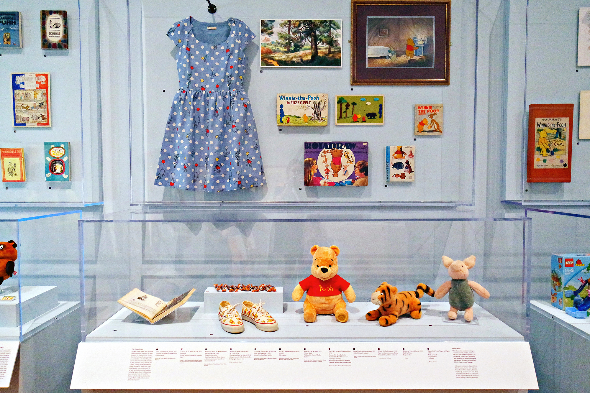 This display from the Winnie-the-Pooh: Exploring a Classic exhibit at the High Museum of Art Atlanta features Winnie-the-Pooh, Tigger, and Piglet stuffed animals, a dress, shoes, artwork, games, books, and more.